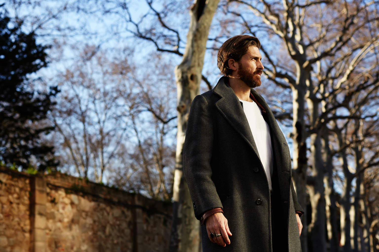 Portrait of well dressed man with beard posing outdoors looking