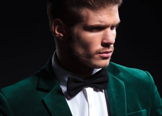 side view of a fashion model in green velvet suit looking away f
